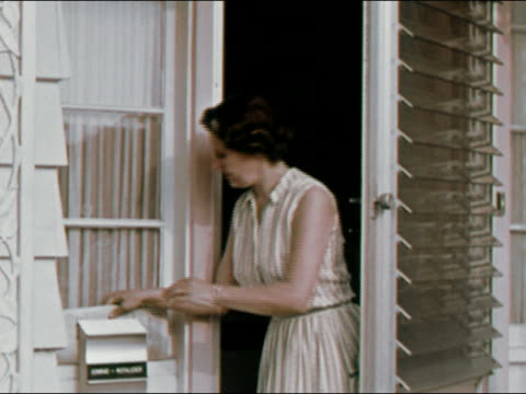 1964 medium shot housewife taking newspaper from behind mailbox, opening it, and reading / long island, new york / audio - stereotypical housewife stock videos & royalty-free footage