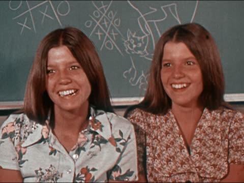 vidéos et rushes de 1970 medium shot identical twin teenage girls talking and laughing in classroom / audio - 1970