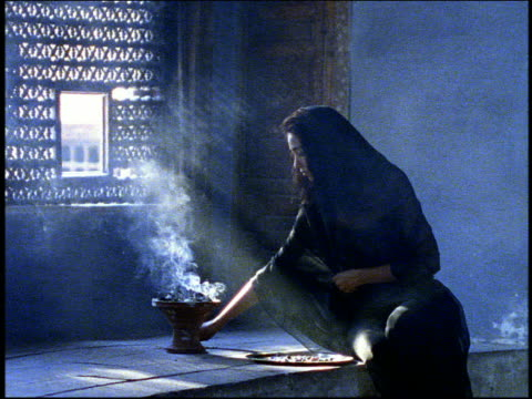 Medium shot incense burning in holder by window / woman in veil kneeling in mosque / Cairo, Egypt