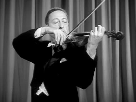 Medium shot Jascha Heifetz playing violin during performance/ USA