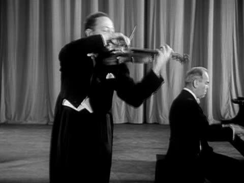 Medium shot Jascha Heifetz playing violin onstage next to pianist during performance/ USA