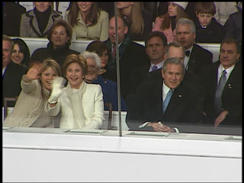 vídeos y material grabado en eventos de stock de medium shot jenna and laura bush waving at cam as bush family watches inaugural parade / audio / wash. dc - 2005