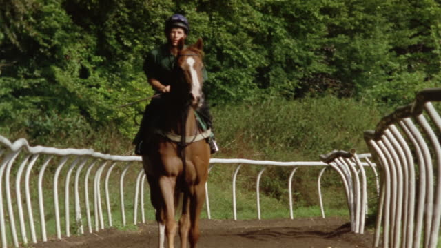 medium shot jockey riding horse on track toward camera/ berkshire, england - herbivorous stock videos & royalty-free footage