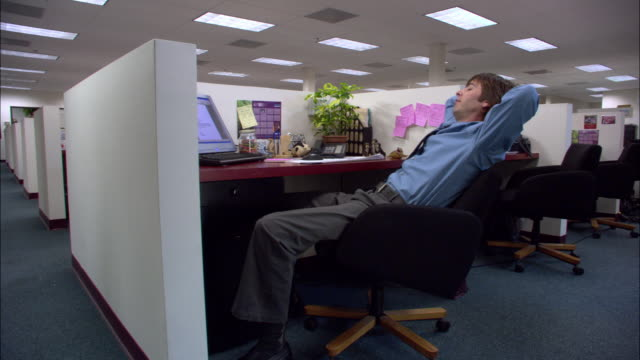 Medium shot jump cuts of male office worker sleeping and playing with office equipment + supplies in cubicle / low angle