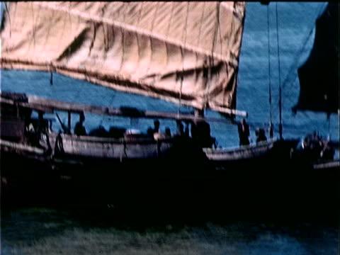 1939 medium shot junk boat passing through harbor/ hong kong - 1939 stock videos and b-roll footage