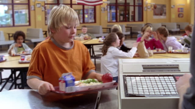 Medium shot kids pay for food in school cafeteria/ cashier pushing buttons on cash register/ Goram, Maine