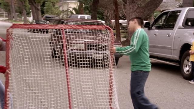 Medium shot kids talking in street / kids moving soccer goal so car can pass / resuming soccer game