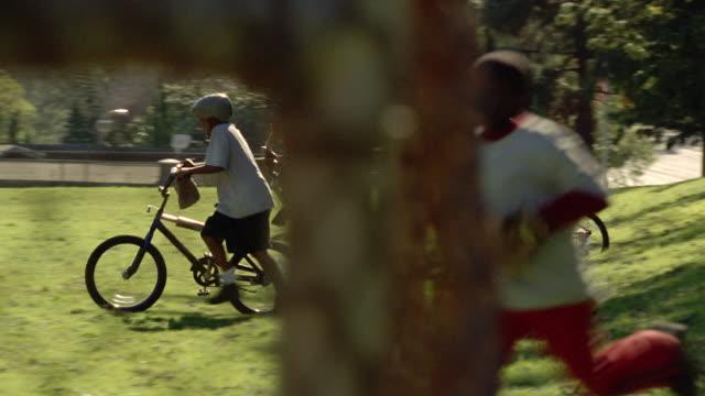 Medium shot kids walking bikes and running downhill carrying sports equipment / dog running behind