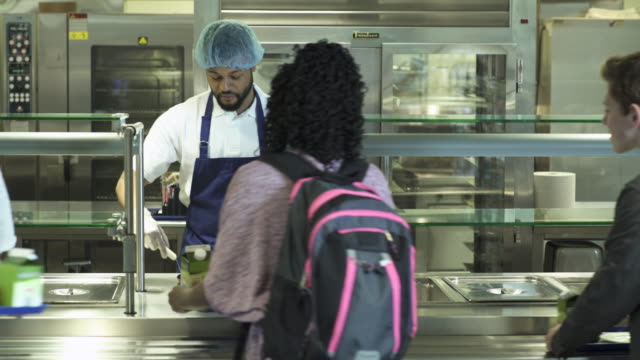 Medium shot kitchen staff serving food for high schoolers