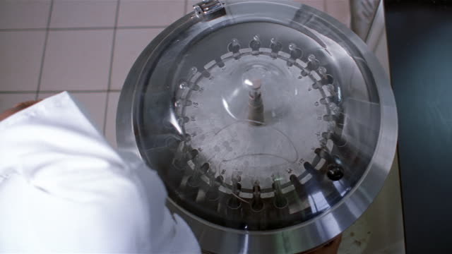 medium shot lab technician closing lid of centrifuge / turning on centrifuge - zentrifuge stock-videos und b-roll-filmmaterial