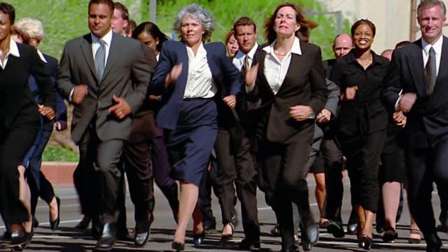 Medium shot large group of business people running across street