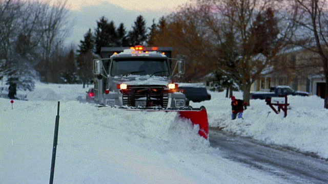 medium shot large truck plowing snow on suburban street - snowplough stock videos & royalty-free footage