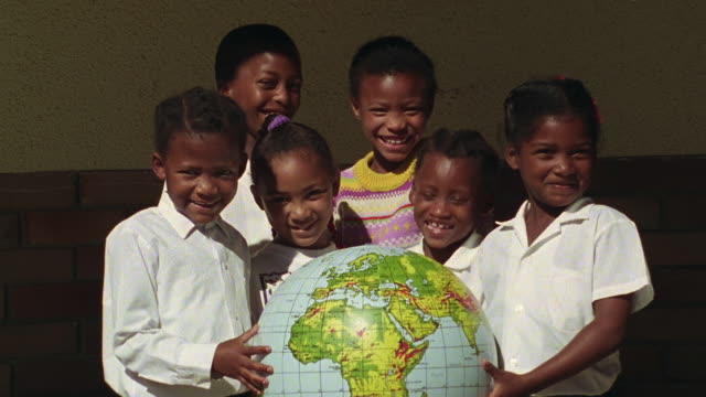medium shot laughing black boy and girls holding up globe outdoors / south africa - villaggio globale video stock e b–roll