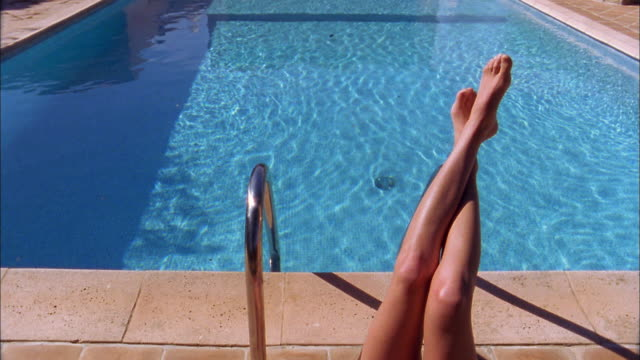 Medium shot legs of woman casually resting over swimming pool / man diving into pool
