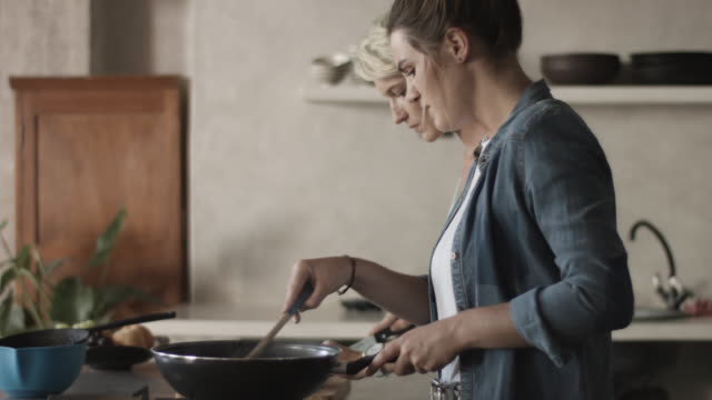 stockvideo's en b-roll-footage met medium shot, lesbian couple cook dinner - avondmaaltijd