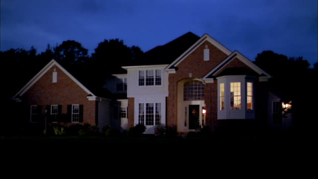 Medium shot lights turning off and on inside suburban house at night
