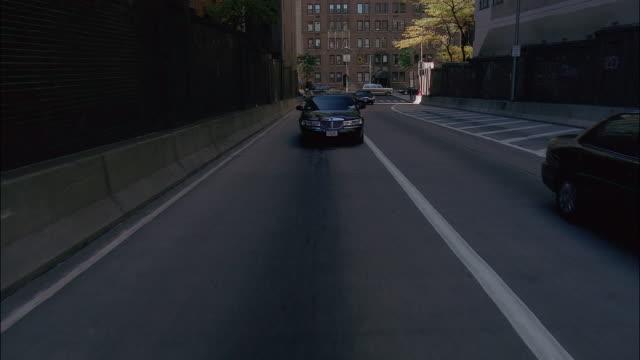 medium shot limousine driving down city street - limousine luxuswagen stock-videos und b-roll-filmmaterial