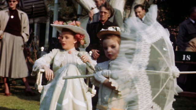1949 medium shot Liza Minnelli as toddler holding parasol on film set / Judy Garland sitting in background