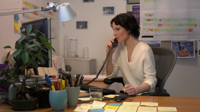 Medium shot lockdown businesswoman sitting at desk typing on computer keyboard, talking on telephone