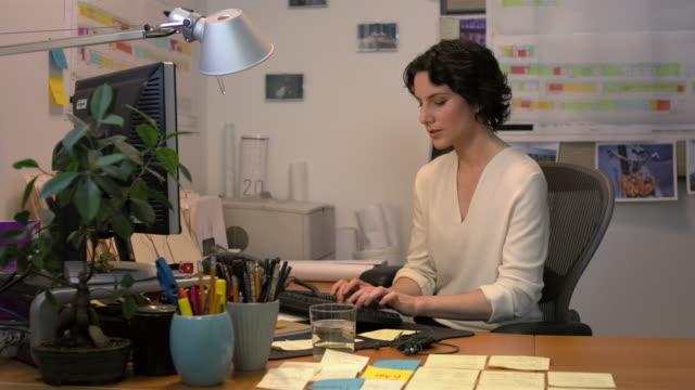 Medium shot lockdown businesswoman sitting at desk typing on computer keyboard, working