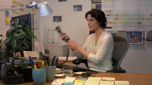 Medium shot lockdown businesswoman sitting at desk, typing on computer keyboard, talking on telephone