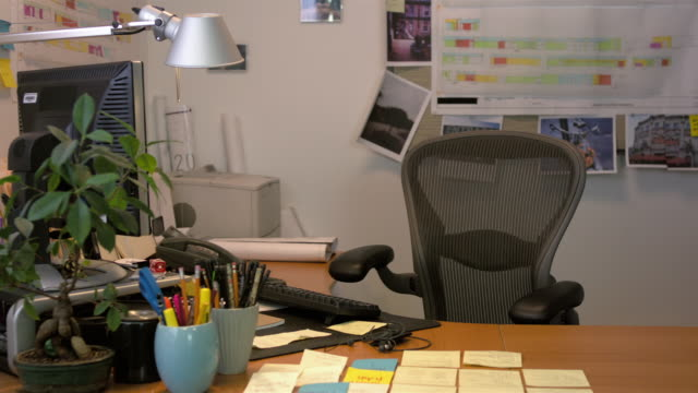 Medium shot lockdown empty chair behind desk in office