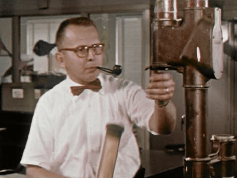 1964 medium shot lockdown new york newsday newspaper man at with pipe puts paper in pneumatic tube / long island, new york / audio - new york newsday stock videos & royalty-free footage