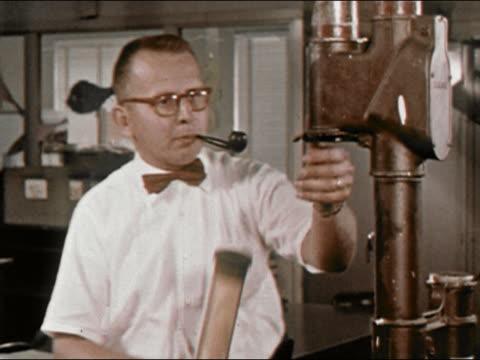 1964 medium shot lockdown new york newsday newspaper man at with pipe puts paper in pneumatic tube / long island, new york / audio - ニューヨークニュースデイ点の映像素材/bロール