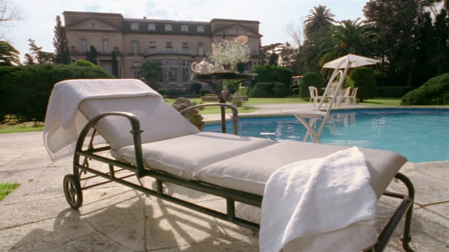 stockvideo's en b-roll-footage met medium shot lounge chair on pool deck outside mansion - zwembadrand