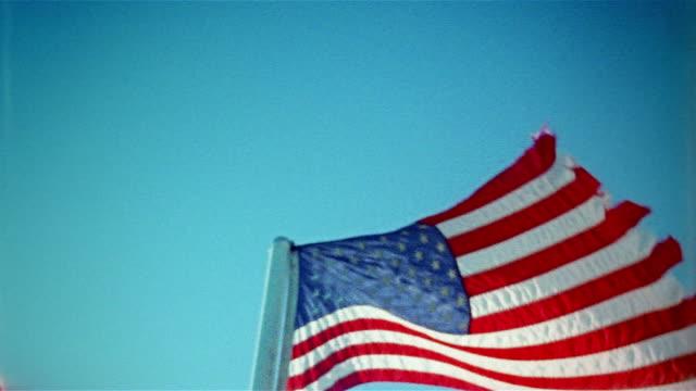 Medium shot low angle American flag waving in wind