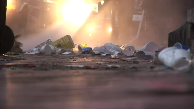 Medium Shot Low Angle - Trash and street being sprayed by water hose / New Orleans Louisiana