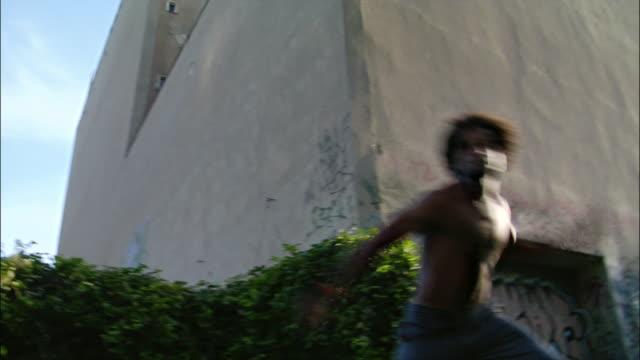 medium shot - low angle view. one mid adult male capoeira dancer performing a backflip. - 離れ技点の映像素材/bロール