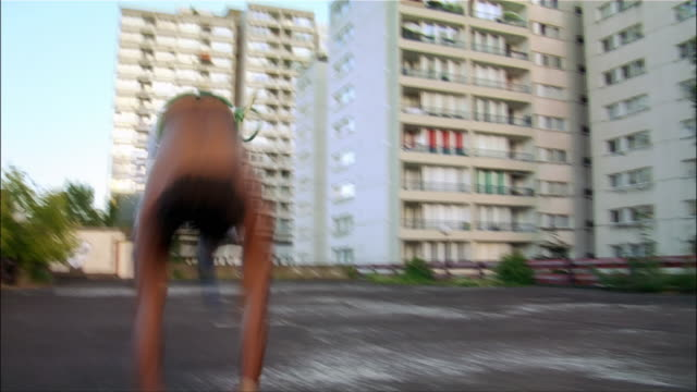 medium shot - low angle view. one young male capoeira dancer performing a backflip. - バク転点の映像素材/bロール