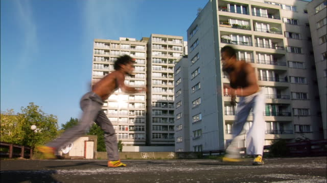 medium shot - low angle view. two male capoeira dancers sparring on roof. - 離れ技点の映像素材/bロール