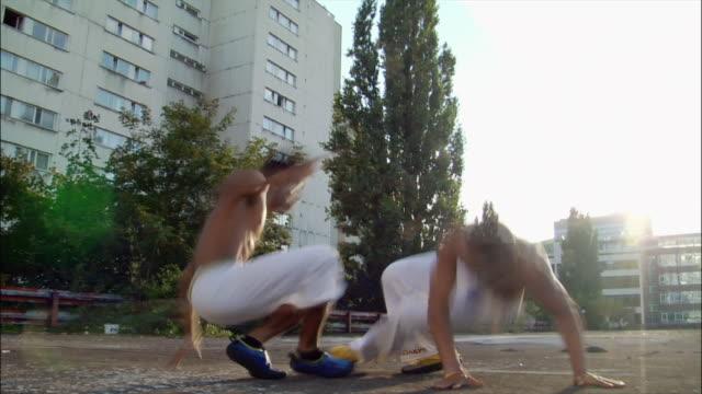 medium shot - low angle view. two male capoeira dancers sparring. - 離れ技点の映像素材/bロール