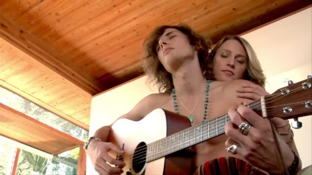 vídeos de stock, filmes e b-roll de medium shot - low angle view. young couple relaxes in bedroom while young man plays guitar. - ventilador de teto