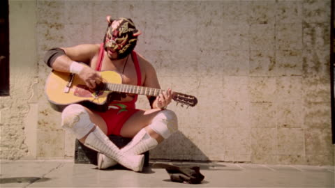 """medium shot luchador """"black tiger"""" playing guitar and singing on street for money/ monterrey, mexico - bizarre stock videos & royalty-free footage"""