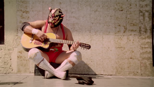 "Medium shot luchador ""Black Tiger"" playing guitar and singing on street for money/ Monterrey, Mexico"