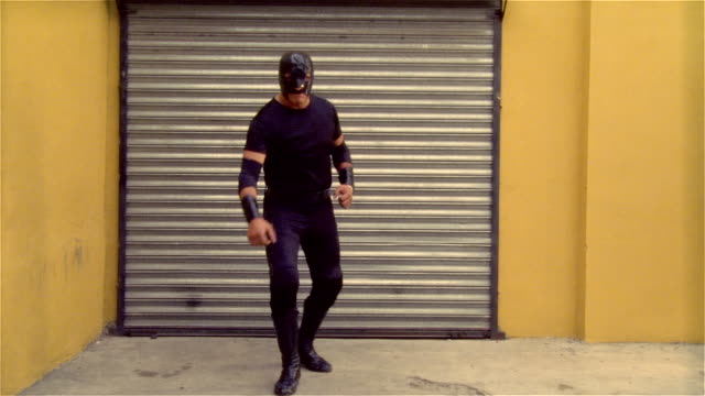 """stockvideo's en b-roll-footage met medium shot luchador """"shadow"""" standing in front of garage door, pointing at camera, raising fist, punching hand/ zoom in flexing muscles/ monterrey, mexico - gympak"""
