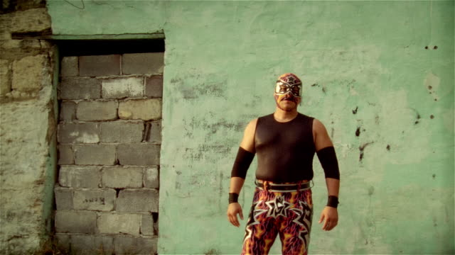 "Medium shot luchador ""Silver Star"" looking at camera and flexing muscles/ Monterrey, Mexico"