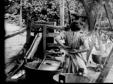 stockvideo's en b-roll-footage met 1910 b/w medium shot maid being put to work in yard by woman of the house  - 1900 1909