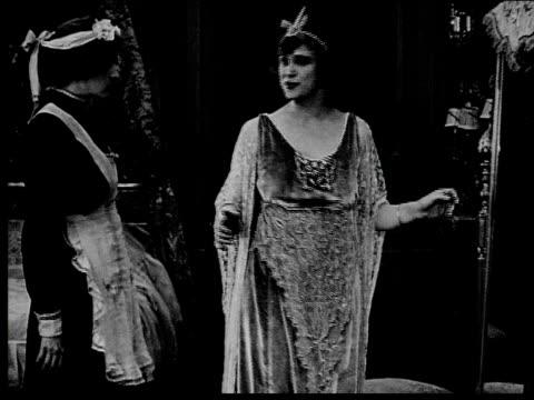 1916 b/w medium shot maid talking to queen as queen looks in mirror/ queen looking worried and running off - hand aufs herz stock-videos und b-roll-filmmaterial