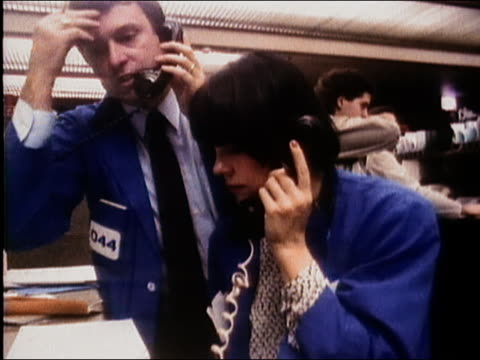 1987 medium shot male and female brokers speaking on telephones / chicago board of trade / audio - 1987 stock-videos und b-roll-filmmaterial