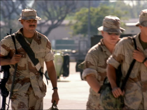 stockvideo's en b-roll-footage met 1991 medium shot male and female soldiers walking holding luggage returning from gulf war / california - 1991