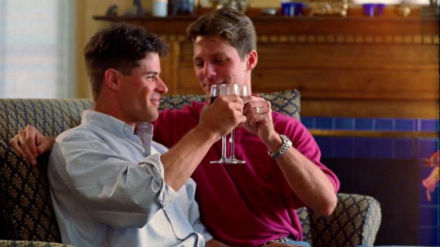 vídeos y material grabado en eventos de stock de medium shot male couple sitting on sofa, drinking toast with glasses of wine - encuadre de tres cuartos
