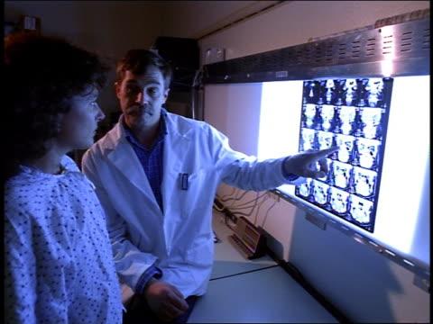 medium shot male doctor explaining x rays to female patient in hospital - untersuchungskittel stock-videos und b-roll-filmmaterial