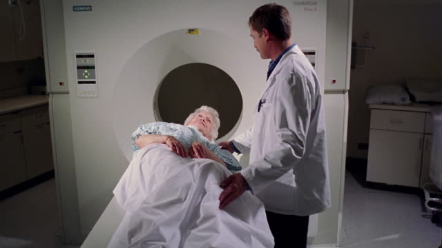 medium shot male doctor giving mri to senior female patient - untersuchungskittel stock-videos und b-roll-filmmaterial