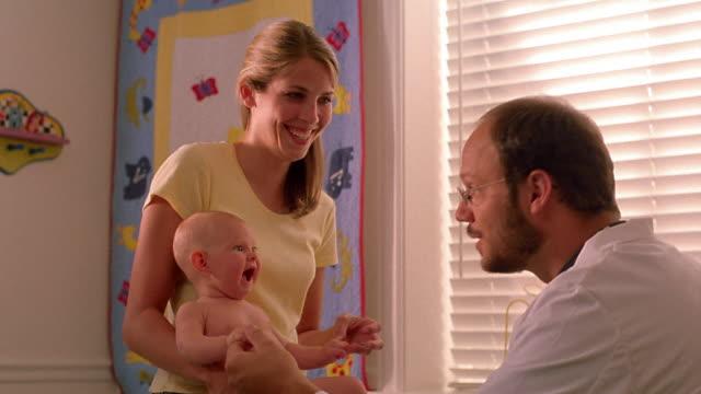 vídeos y material grabado en eventos de stock de medium shot male doctor talking to baby / woman holding baby and smiling - menos de diez segundos
