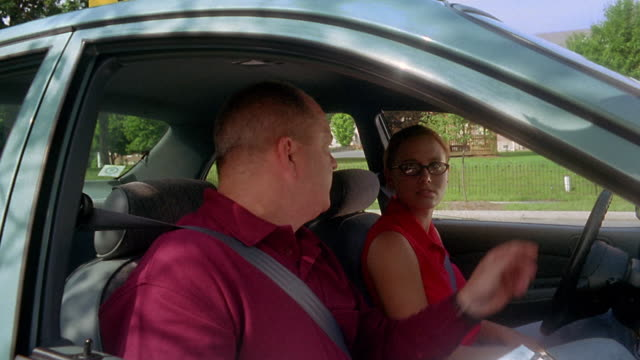medium shot male driving instructor pointing out rear and side view mirrors to female student driver in car - driving test stock videos and b-roll footage
