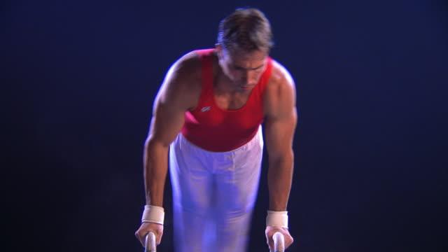 vídeos de stock e filmes b-roll de medium shot male gymnast performing routine on pommel horse - fotografia de três quartos